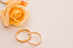 Wedding rings with a yellow rose. Wedding rings on a cream background with a yellow rose with space to add copy Stock Photography