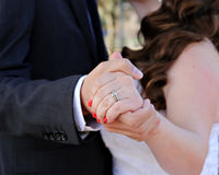 Wedding Romantics. Newly married couple enjoy a quiet embrace showing the wedding ring on hand Stock Photography