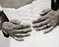 Wedding Romantics. Newly married couple enjoy a quiet embrace showing the wedding ring on hand Stock Image
