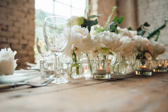 Wedding room decorated loft style with a table and accessories. Wedding room decorated loft style with a table and other accessories candles , peonies , bulbs Stock Photography