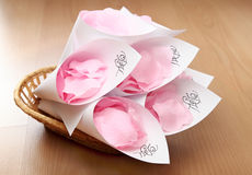 Wedding rose petals in basket. Wedding rose petals wrapped in paper with initials of bride and groom royalty free stock photos