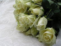 Wedding roses. Photograph of a bouquet of creamy white roses on top of a fabric with a pattern of roses Stock Photo