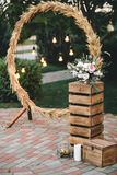 Wedding round arch in rustic style decorated with grass hay field color and retro light bulbs. Near the wooden boxes. Wedding round arch in rustic style Stock Photos