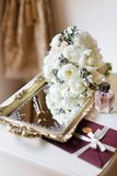Wedding rustic bouquet, decorative mirrored tray, bottle of perfume and envelope letter with stamp on nightstand. Bridal room inte. Bridal morning concept in stock photo