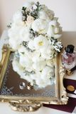Wedding rustic bouquet, decorative mirrored tray and wedding rings on nightstand. Bridal room interior. Composition with wedding a. Bridal morning concept in stock photography