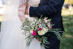 Wedding rustic bouquet with roses. Bride in a white dress and a groom in a suit are holding a beautiful bouquet of white, pink flo Stock Photo