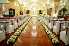 Wedding Scene. Chairs and flowers at an indoor wedding Royalty Free Stock Photography