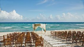 Wedding by the sea in Cancun Mexico. Chairs and flowers for a wedding in Cancun mexico by the beautiful ocean Stock Image