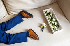 Wedding set of boutonnieres of roses in a wooden box on the sofa stock photo