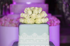 Wedding set-up. Wedding cake, close-up. Beautiful flowers decoration for wedding cake. Huge cake blurred on the background royalty free stock image
