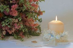 Wedding set up with a candle. Single candle in a wedding garter with a bouquet of dried flowers and two golden rings on festive embroidered white tablecloth Stock Image