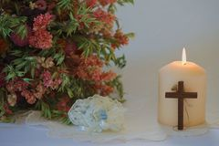 Wedding set up with flowers, candle, wedding garter and cross. Single candle with a wooden cross, a bouquet of dried flowers and a wedding garter on festive Royalty Free Stock Images