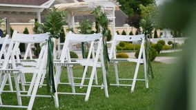 Wedding set up in garden, park. Outside wedding ceremony, celebration. Wedding aisle decor. Rows of white wooden empty