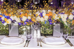 Wedding set-up. Wedding table setup. Beautiful flowers decoration for wedding dinner with white, purple and yellow flowers Stock Photography