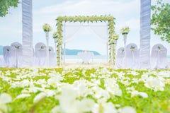 Wedding setting on the grass green on beach. stock photo