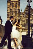 Wedding sexy couple near caste on palace outdoor. Young wedding couple of sexy girl with brunette hair and pretty face in white bride dress and handsome men in stock photo