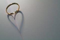 Wedding shadow. A ring casting a heart shadow onto a book Stock Photos