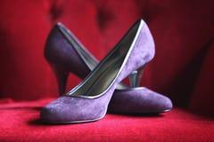 Wedding Shoe. A beautiful purple high heels arranged on a red sofa Stock Photo