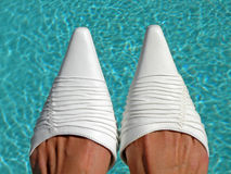 Wedding Shoes. Detail of elegant white shoes pictured against blue water surface Royalty Free Stock Image