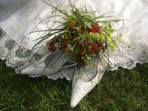 Wedding Shoes. Arranged with a flower arrangement and the edge of the bridge's dress.  Grass visible in lower part of the photograph Stock Image
