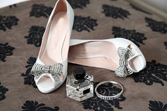 Wedding shoes. White wedding shoes with silver bow, perfume bottle and bracelet Stock Photography