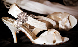 Wedding shoes. Wedding preparation: shoes ready to be worn with wedding gown in background. Focus on the jewels Royalty Free Stock Image