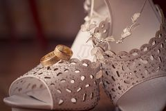 Wedding shoes. A pair of women's wedding wite shoes and two gold rings Royalty Free Stock Photos