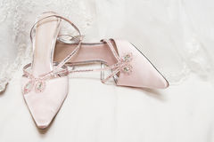 Wedding Shoes. Light Colored wedding shoes on a white gown Royalty Free Stock Photo