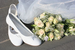 Wedding shoes. The wedding white shoes, bouquet and easy addition are on ground Royalty Free Stock Images