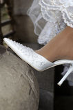 Wedding shoes on barefooted legs of the bride stock photography