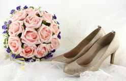 Wedding shoes and a bouquet of flowers Stock Photos