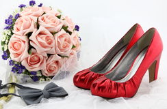 Wedding shoes and a bouquet of flowers Stock Images