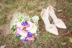 Wedding shoes with bouquet Royalty Free Stock Images