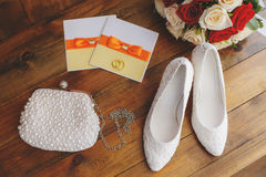 Wedding shoes and bouquet of red and white roses. On wooden background, marriage concept Royalty Free Stock Image