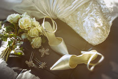 Wedding shoes with bouquet of  roses  on chair Royalty Free Stock Images