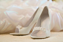 Wedding shoes for the bride. White shoes of the bride standing against a wedding dress fragment Stock Photography