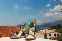 Wedding shoes of the bride against the background of mountains and the sea. Royalty Free Stock Image