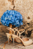 Wedding shoes of a bride on a stone background and a blue bridal bouquet Royalty Free Stock Photography