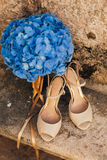 Wedding shoes of a bride on a stone background and a blue bridal bouquet Stock Images