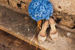 Wedding shoes of a bride on a stone background and a blue bridal bouquet Royalty Free Stock Photos