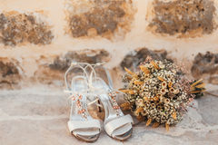 Wedding shoes of a bride on a stone background and a white bridal bouquet Stock Images