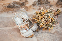 Wedding shoes of a bride on a stone background and a white bridal bouquet Royalty Free Stock Photo