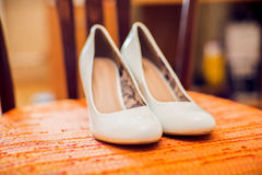 Wedding shoes cream color on the chair royalty free stock images