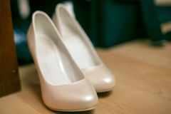 Wedding shoes cream-coloured white. On the floor Royalty Free Stock Image