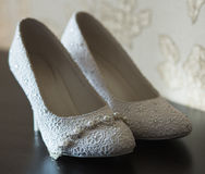 Wedding shoes on the desk. White wedding shoes on the desk Royalty Free Stock Photos