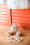 Wedding shoes, dress and pearl necklace. Wedding accessories. Stock Image