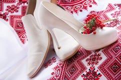 Wedding shoes is on a embroidery ukrainian background. White elegant, stylish wedding (bridal) shoes (bride's and groom's ) is on a red embroidery ukrainian Stock Photography