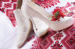 Wedding shoes is on a embroidery ukrainian background. Stock Photography
