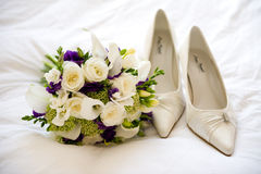 Wedding shoes and flowers Stock Photos