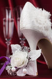Wedding shoes and flowers on the background of two glasses Royalty Free Stock Photo